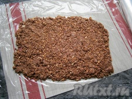 На лист пищевой плёнки выложить массу из печенья в виде прямоугольника, тщательно разровнять.