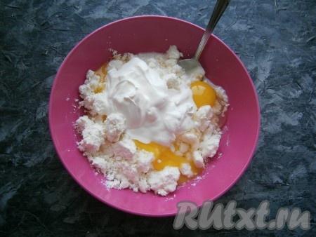 Творог перемешать, добавить сметану, сырые яйца.