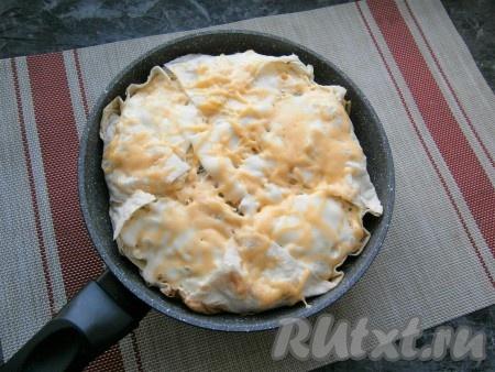 Между бортиками сковороды и основным лавашом влить 20 мл воды. Сковороду поставить на минимальный огонь, накрыть крышкой и готовить пирог из лаваша с сыром около 15-17 минут.