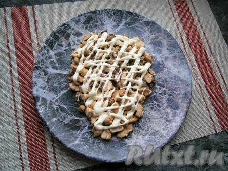 Куриное филе с грибами остудить и выложить на большую плоскую тарелку в виде головы быка, нанести щедрую сеточку из майонеза.