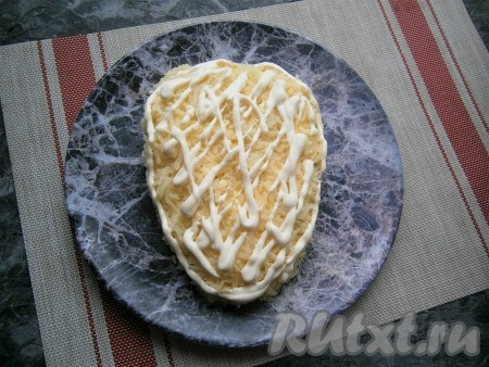 Далее идёт слой натёртого на средней (или мелкой) тёрке картофеля, немного посолить, смазать сеточкой из майонеза.
