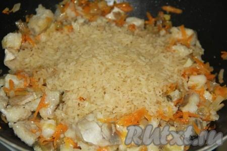 Рис промыть, а затем всыпать в сковороду с минтаем и овощами.