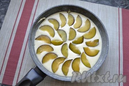 Выложить подготовленное тесто в смазанную сковороду. Сливы освободить от косточек и нарезать их дольками, которые разместить по верху теста.