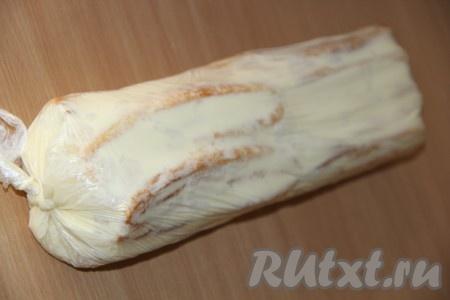 Плотно завернуть полоски теста с кремом в пищевую плёнку, сформировав полено. Концы пищевой плёнки замотать.
