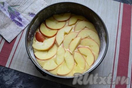 В форму выложить тесто и разровнять его. Сверху в один слой разместить дольки яблок, очищенных от семян.