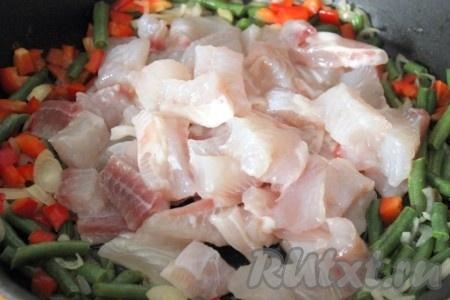 Затем к овощам на сковороду добавить рыбу, посоленную и нарезанную на кусочки как на фото), и тоже немного обжарить.