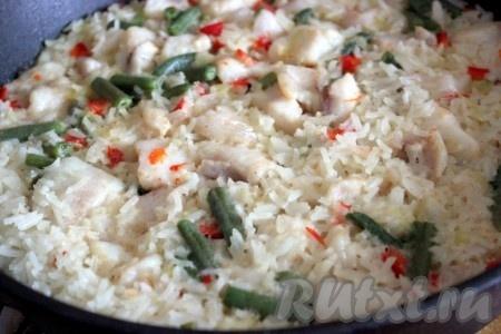 Довести до закипания и тушить рис с рыбой на среднем огне до готовности риса.
