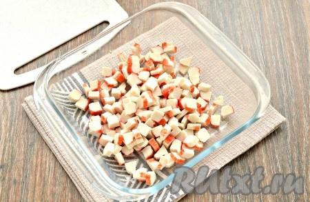 Заранее сварить по отдельности куриное филе и яйца. На варку яиц потребуется минут 8-10 с начала кипения воды. Куриное филе нужно будет отварить в течение минут 25 с момента закипания воды. Отваренные куриное филе и яйца остудить. Разморозить крабовые палочки, затем достать из упаковки и, сняв плёнку, нарезать на мелкие кубики, выложить в достаточно глубокую миску.