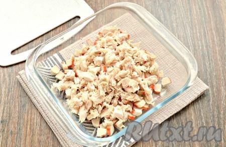 Остывшее куриное филе нарезать небольшими кусочками и выложить к крабовым палочкам.