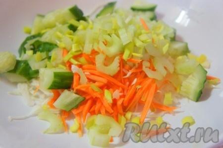 Огурец крупно нарезать, сельдерей очистить и нарезать тонкими пластинками, добавить мелко нарезанный зеленый лук. Добавить нарезанные овощи к капусте и моркови.