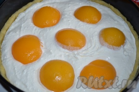 На тесто равномерно распределяем начинку. Раскладываем половинки консервированных персиков, немного вдавливая их в творожную массу.