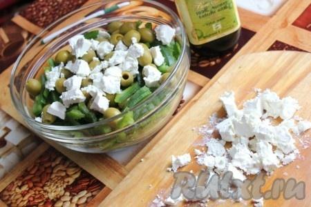Добавить в овощной салат оливки и брынзу, поломанную на кусочки.