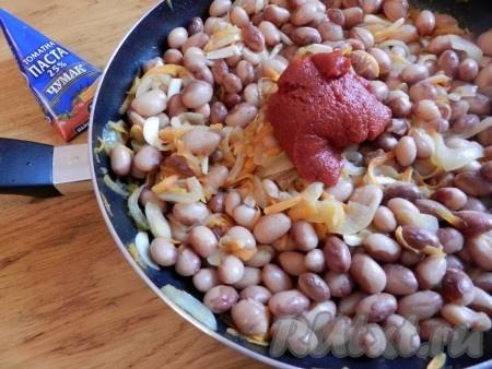 На растительном масле обжарить лук и морковь, добавить фасоль, затем чеснок и томатную пасту. Добавить соль и специи. Разбавить водой от варки фасоли и потушить минуты три все вместе.