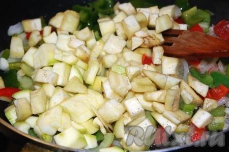 Затем добавить очищенные  от кожуры и нарезанные небольшими кубиками баклажаны и кабачки. Обжаривать 10 минут.