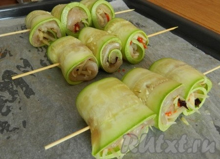 Скрутить рулетики из кабачков с куриным мясом, сколоть их шпажками и запечь при 180 градусах 25 минут.
