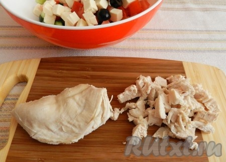 Оливки разрезать пополам. Нарезать куриное мясо кубиками.