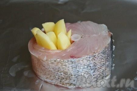 На фольгу кладем стейк судака и картофель так, как показано на фото.