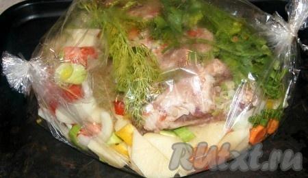 В рукав положить овощи, на них уложить свиные ребрышки в специях, дополнительно положить пучок зелени.