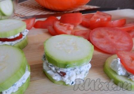 На кружок кабачка положить 0,5-1 чайной ложки сырной массы, затем кусочек помидора, еще немного сырной массы и накрыть кружочком кабачка, чуть придавить.