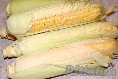 Приготовить кукурузу для варки. Для этого очистить верхние грубые листья, а внутренние (светлые и нежные) оставить. Можно очистить и всю кукурузу, тут кому как удобнее. Я люблю чистить после варки.