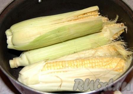 Уложить початки кукурузы вместе с листьями в болюьшую кастрюлю. Если у вас дома нет большой кастрюли, то можно разломать каждый початок на пополам.