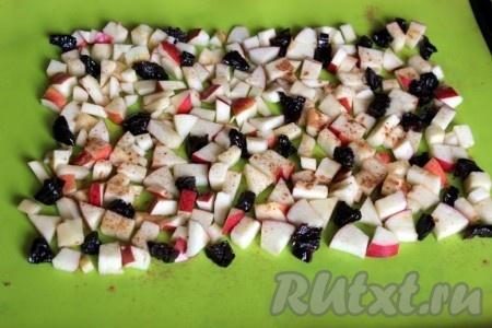 Включите духовку на 180-200 градусов. Для начинки рулета быстро нарежьте яблоки небольшими кубиками или дольками и чернослив на 2-4 части. Уложите фрукты на силиконовый коврик или бумагу для выпечки на противне, посыпьте корицей.