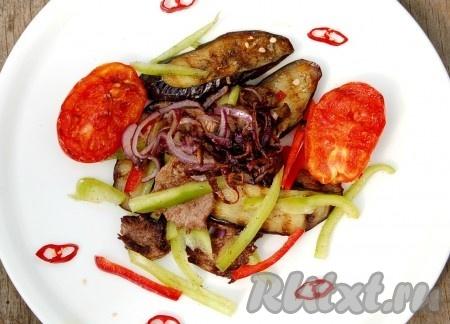 Выложить готовый салат на тарелку, а сверху пристроить обжаренный лук и помидоры.