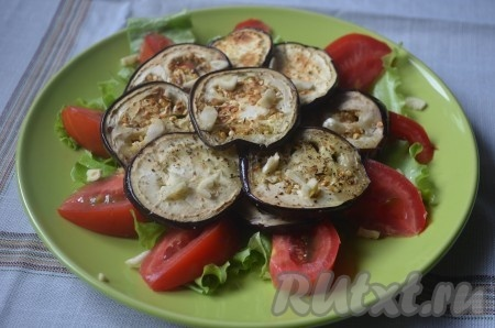 На помидоры выложить обжаренные баклажаны. Посыпать салат рубленным чесноком.