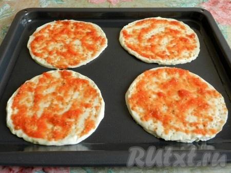 Слоеное тесто немного раскатать и вырезать из него 4 заготовки для мини пиццы. Противень смазать растительным маслом, выложить круги из теста, проколоть из вилкой, смазать приготовленным ранее соусом.