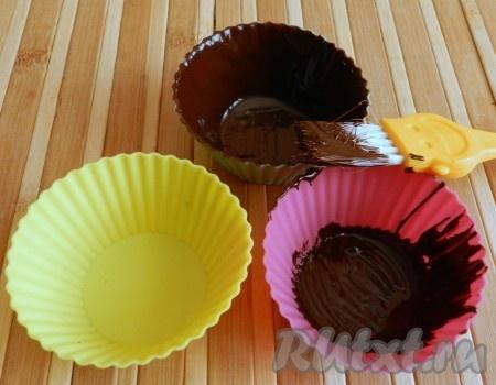 С помощью кисточки нанести слой шоколада на дно и стенки силиконовых формочек. Смазывать формочки не нужно.
