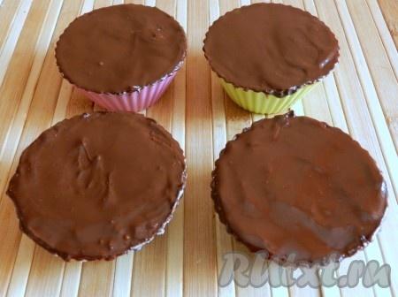 Поверх творога равномерно распределить слой шоколада и снова убрать глазированные сырки в холодильник на 15-20 минут. Затем аккуратно освободить глазированные сырки от силиконовых формочек и подавать.