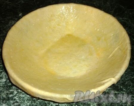 Берем теперь этот большой кусочек и раскатываем его так, чтобы он накрыл дно и бока нашей формы, и еще чуть-чуть свисал. Теперь наматываем тесто на скалку, переносим на форму. Выстилаем им нашу форму. Края теста пусть свисают. Теперь растопим сливочное масло и смажем им тесто.