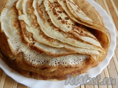 Приготовить тонкие блины.  Для этого в кефире растворить соду, подождать некоторое время. Затем смешать кефир и молоко. Яйца взбить с сахаром и солью, соединить с молочной смесью. Постепенно высыпать муку. Добавить растительное масло, все тщательно перемешать. Тесто получится однородное, не густое.  Жарить блины на сковороде без добавления масла с двух сторон. Блины должны получиться тонкими и эластичными. Для этого пирога мне понадобилось 18 блинов.