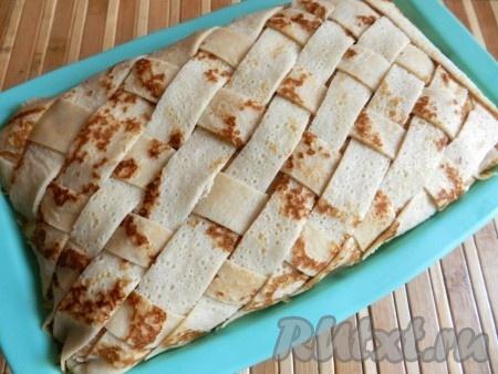 Два блинчика нарезать полосками 1х1 см и сделать декоративную плетенку на поверхности блинного пирога с грибами и мясом.