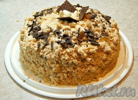Вокруг торта все смазать кремом, крошками из безе. Сверху посыпать тертым шоколадом. Можно добавить несколько орешков. Вкуснейший бисквитный торт, приготовленный в домашних условиях, готов.