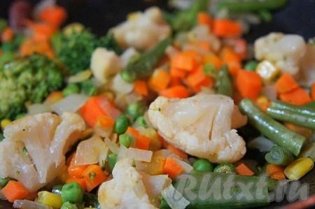 К чуть обжаренной моркови и луку добавить овощную смесь, перемешать. Накрыть крышкой и немного потушить на медленном огне около 5 минут.