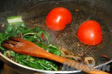 Обжаривать все вместе 1 минуту, затем содержимое сковородки сдвинуть на одну сторону. На свободное место положить разрезанные пополам помидоры срезом вниз и слегка их обжарить.