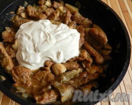 В сковороду с говядиной и грибами влить сметанный соус, перемешать, накрыть крышкой и тушить 10 минут.