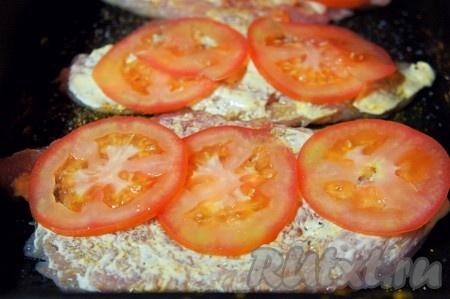 Тем временем духовку разогреть до 180-200 градусов. Помидор вымыть и тонко нарезать. Сыр натереть на мелкой тёрке. Куриные грудки смазать майонезом, выложить нарезанные помидоры.
