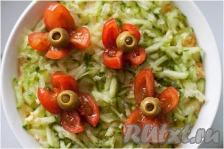 Завершающим этапом салата служит огурец, натертый на крупной терке. Украшаем салат помидорами черри с оливками.
