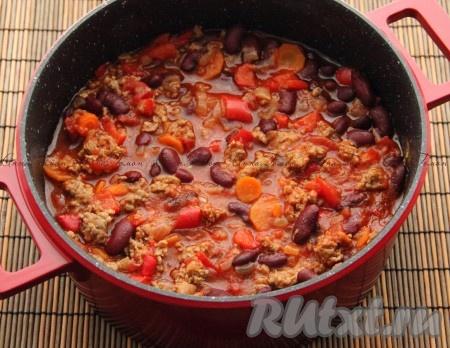 2. В большой кастрюле нагреть масло на слабом огне и обжарить лук до золотистого цвета. Добавить измельченный чеснок и морковь. Увеличить огонь до среднего и добавить говядину. Обжаривать, постоянно помешивая, около 10 минут. Приправить и готовить еще минуту. Добавить томаты, уксус и говядину, накрыть крышкой и тушить около 30 минут. В последнюю очередь в кастрюлю добавить фасоль и болгарский перец и тушить еще 10-15 минут.
