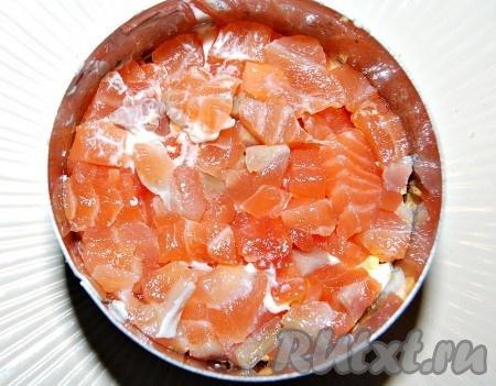 Соленую рыбу мелко нарезать и половину порции уложить на слой из желтков. Этот слой также смазать небольшим количеством майонеза.
