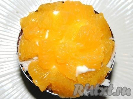 Апельсины аккуратно отделить от белых пленок и использовать только желтую мякоть.  Нарезать мелкими сегментами и уложить поверх сыра.