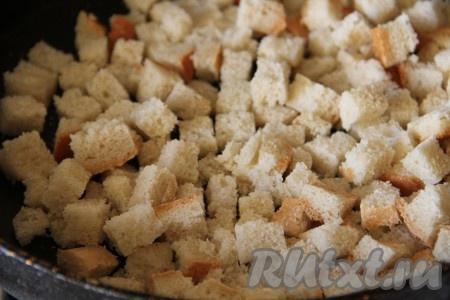 Батон нарезаем на кубики и поджариваем на сухой сковороде минут 10. Пока хлеб не подсушится и не приобретет золотистую корочку.