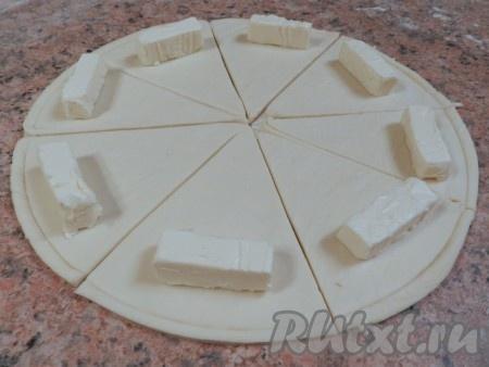На край каждого сектора положить по 1/3 кусочка сыра Kiri, затем завернуть каждый сектор из дрожжевого слоеного теста в рогалик от края к центру.