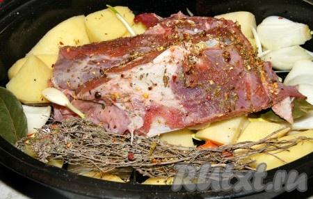 Натереть баранину со всех сторон специями, уложить на слой овощей, рядом пристроить травы.
