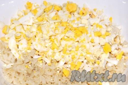 Добавить нарезанные яйца в миску к рису.