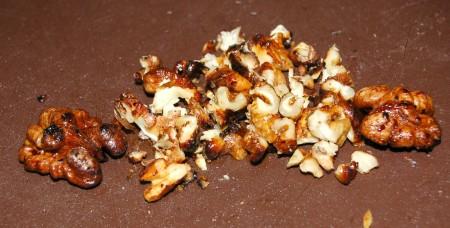 Выложить на доску готовые орехи и с помощью ножа  нарезать их на мелкие кусочки. Это будет дополнением к салату с курицей и рисом.