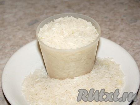 Когда масло с карри начнет кипеть, добавить сухой рис. Размешать деревянной ложкой. Обжаривать 5 минут.
