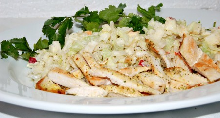 Сервировать салат с капустой, сельдереем и яблоком на тарелку вместе с кусочками обжаренного куриного филе.